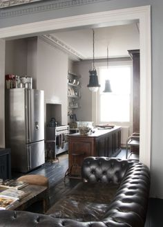 -black leather sofa -dark wooden flooring -the light grey and earth toned walls blance out the coours in this room -love the chrome fridge