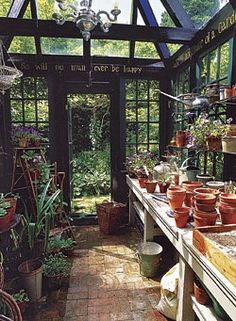 Inside the greenhouse, dry-laid brick floors allow excess water to soak into the ground, while a long counter affords plenty of space for starting seeds and potting up containers. Window shelves are lined with plants, while potting soil and supplies are stashed under the counter.  My personal heaven!