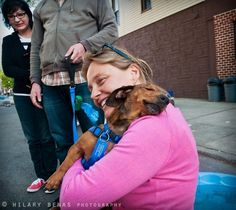 """one photo that proves that dogs feel gratitude:  Eva, a rescue-foster mom from Brooklyn, saved this one-eyed dachsund mix from a high-kill shelter in Alabama.  Named Captain Morgan, he's now happily adopted and was reunited with Eva at a Brooklyn block party.  As soon as he saw her, he jumped into her arms to say """"thank you""""."""
