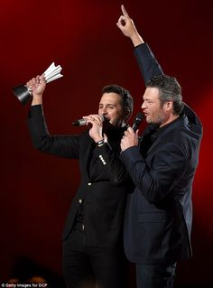 Top honor: Luke Bryan held up his trophy for Entertainer of the Year as co-host Blake Shelton looked on