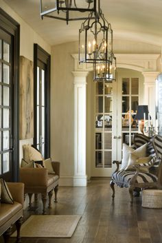 Black French doors with black trim though the rest of the millwork is white; multiple lanterns lined up horizontally to echo the linear nature of the space