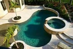 """Here's another pool wrapping a larger body around a jacuzzi. The swimming pool features an ultra-shallow """"beach"""" style end, while the jacuzzi stands on a level above. Gunite Swimming Pool, Swimming Pools Backyard, Swimming Pool Designs, Backyard Beach, Tropical Backyard, Pool Spa, Diy Design, Design Ideas, Piscina Spa"""