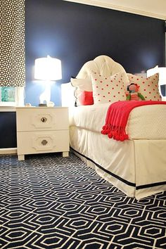 Sarah Catherine Designs | Navy  Coral | Geometric Print Rug | Bright Pom Pom Throw | Area Rug | White Headboard | Navy Walls