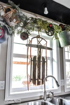 Christmas junk wheel wreath valance and sleigh in window / A junky Christmas kitchen / salvaged finds used to deck out this kitchen for Chri...