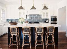 White cabinets, navy island, grey blue tile backsplash modulates that transition from light to dark. Three gold pendants and three rattan and navy bistro stools tie it all together. So simple, so smart, so satisfying.