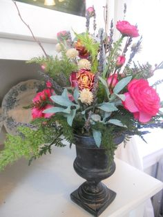 Beautiful arrangement filled with dried roses and silks set in a black stone urn.