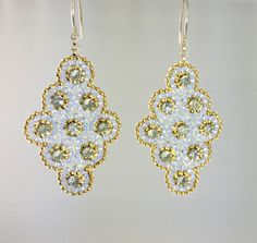 Elegant earrings hand made by bead weaving small seed beads onto a diamond shaped contour. A small swarovski crystal enhances the center of each little circular flower for an overall texture of subtle sparkle. Neutral tones of soft blue with light charcoal sparkle trimmed by a gold edging outlining their shape. Ear wires are quality gold filled with a stylish unique curvature. Hangs from gold filled links connecting to beadwork providing a free flow. Extremely light weight. Earring measures…