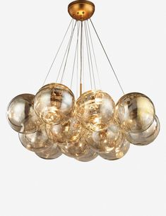 Well lit. A cluster of gold tinted globes is both a modern and glamorous statement chandelier for over a dining table.