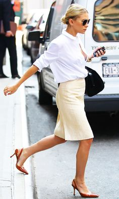 Ashley Olsen wears a white button-down blouse, pencil skirt, slingback pumps, black bag, and aviator sunglasses