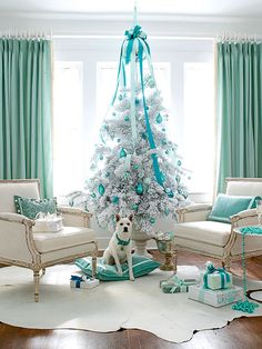 A classic green tree with red and gold trimmings would not have suited this all white-and-teal living room. Instead, a flocked Christmas tree with turquoise and silver ornaments looks modern and chic while still in keeping with the glamour and function of a traditional tree. (Photo: Monica Buck)