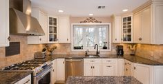 Painted white kitchen cabinets with custom range hood and oiled bronze hardware and faucet.
