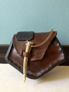 Handmade Leather Hip Bag // Belt Pouch    Handcrafted, thick heavy leather, belt loops.  Has a vintage look, but I am not sure it is.  Front flap with antler closure. Leather is very  firm/hardened. No interior pockets.    Measures; 7 width at widest point, 5.5 height at tallest  point, approx. 2.5 depth.    This is a very rustic, gorgeous piece. I also have  a larger one listed.    Thanks for dropping in.    ships priority with tracking