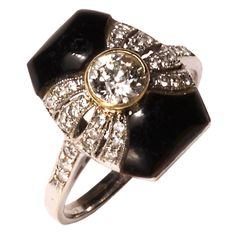 Art Deco Diamond Onyx Ring  c.1920  A cushion shaped onyx is tied in a bow of european full cut diamonds that spill to the shoulders of this elegant Art Deco ring. Set mid center in a gold bezel, is a round european cut diamond of approximately .50 cts in weight. The ring setting is hand made of solid gold and platinum and filigree open work. The lines of design are neat and clean. Black and white stones are a hallmark of Art Deco design.