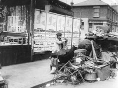 An old woman evicted from her Croydon home with all her possessions, 1913. Behind her a hoarding advertises plots in a nearby housing estate...