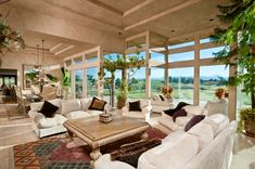 Luxury family room with floor-to-ceiling windows and white sofas.