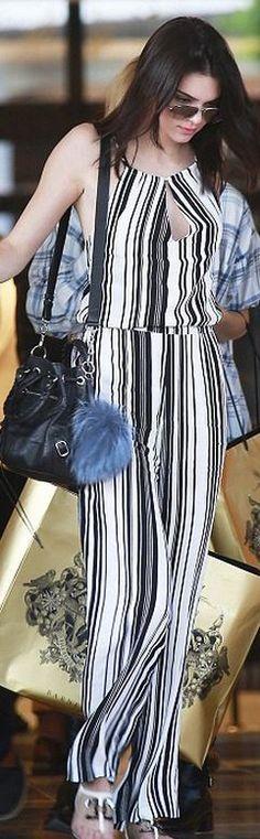 White stripe jumpsuit, black leather handbag, blue key chain, flat sandals, and aviator sunglasses