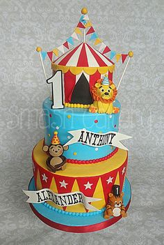 Circus First birthday cake, with big top tier, fondant bunting, fondant animal figurines, and gumpaste lettering.