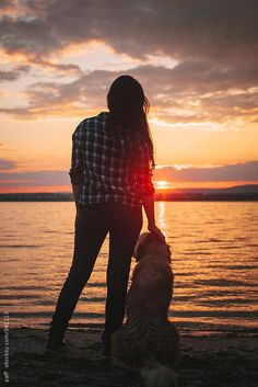 Girl watching the sunset with her dog by paff   Stocksy United
