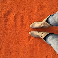 Leaving footprints in the red sand of the outback.