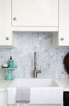 Farmhouse sink, Moen Align Faucet, Carra marble backsplash. Beautiful white IKEA SEKTION GRIMSLOV kitchen with aqua and green accents, a gorgeous marble hexagon backsplash, and quartz countertops. | JustAGirlAndHerBlog.com