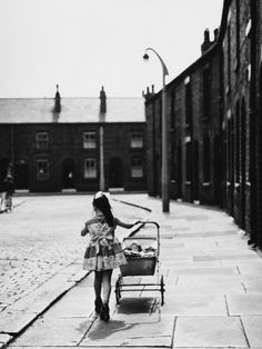 a little girl in a pretty dress wearing high heels which are far too large for her feet, pushes her toy pram along a street in wigan, 1961 [original] © shirley baker Vintage Photographs, Vintage Photos, Shirley Baker, Blackpool Beach, Time Pictures, Street Portrait, Portraits, Slums, Photo Black