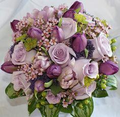 LOVE this bouquet, but not a fan of the big leaf things.  Shades of Lilac Tulips, Roses and Wax Flower, in a handtied posy.