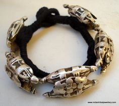 India   Vintage old silver bracelet from Rajasthan   Five hollow silver pieces are woven onto a string cord.