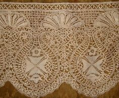 Usually a flower is depicted as a circular rayed motif with woven leaves as petals.The upper ground with woven leaves and the 'X' in each grid is a sign of better quality work.