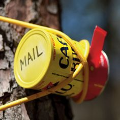 Kid mailbox- Use the hammer and nail to make a hole in the can's side about 2 inches above the bottom rim.  Cut a rectangular flag from the extra lid, use the nail to make a hole in it near one end, and secure it to the can with a brad fastener (watch out for sharp edges).  Use bungee cords to secure the can to a tree or post, and leave a pad and pen inside for jotting notes.