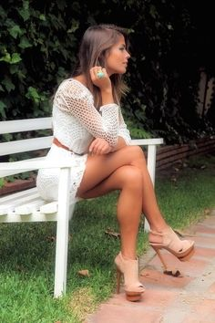Beauty waiting in the park with crossed legs wearing a short dress and sky high heels