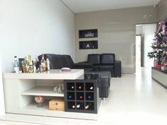 Sala de TV em com painel e móvel em laca bege e preto.