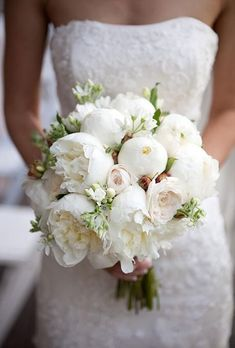 An all-white bouquet with lush peonies and garden roses | Brides.com #weddingflowers