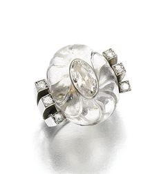 ROCK CRYSTAL AND DIAMOND RING, RENÉ BOIVIN, 1932.  The fluted rock crystal inset with an oval diamond, between shoulders set with circular-cut diamonds, size 511/2, French assay marks.