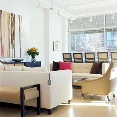 Let the Sun Shine-The hard edges of contemporary design can feel severe. But with plenty of sunlight and rich textures, the space becomes warm and inviting. The simple creamy-hued sofas are dressed up with brown and pink throw pillows. The accents coordinate with the modern painting on the wall.