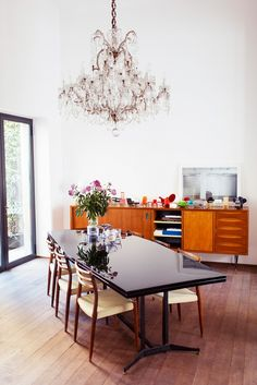 A traditional yet modern dining space with retro console table, vase of flowers, and crystal chandelier // Italian design