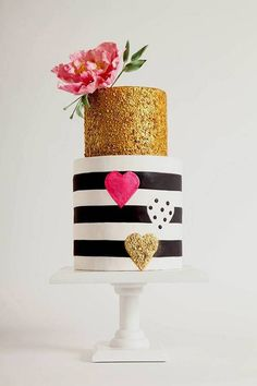 black, white, and gold wedding cake with hot pink heart