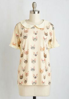 Rely on this jersey knit top for 'aww-inspiring' style! Illustrated with kitties galore, accented with a Peter Pan collar, and finished off with ruffled sleeves, this pale yellow blouse will have people purring over your feline flair.