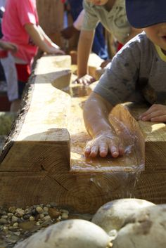 Children playing with a log flume stream
