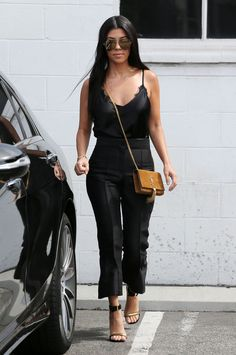 Wearing a black silk cami, high waisted trousers, black and gold stilettos and a YSL crossbody.