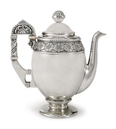 A Fabergé silver coffee pot, Moscow, 1908-1917. In the neo-Russian style, the upper rim, shaped handle, and ball finial, with stylized floral decoration, and pomegranate finial chased with stylized floral or vegetal ornament, the handle with mammoth ivory insulators.
