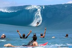 """FRENCH POLYNESIA, TEAHUPOO : Takanui Smith (Rear) rides a wave as fellow surfers and filming crew reacts during the shooting of a remake of the 1991 classic """"Point Break"""" on September 11, 2014 in the Hava'e pass in Teahupoo, on the French Polynesian island of Tahiti. The American action thriller film directed by Ericson Core, starring Edgar Ramirez, Luke Bracey, Teresa Palmer and Ray Winstone, is a remake of the 1991 film then directed by Kathryn Bigelow. AFP PHOTO / GREGORY BOISSY"""
