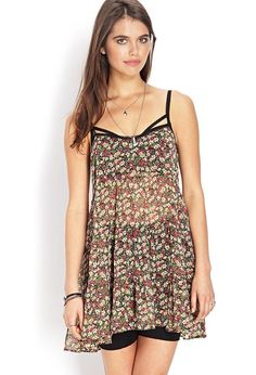 A tiered sheer smock dress featuring a floral pattern. Scoop neckline. Adjustable shoulder straps...