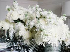 Floral elements are often the most expensive part of tabletop decor; however, supermarket or farmer's market flowers can look chic with the proper editing. To create a white-on-white floral centerpiece that's elegant and cost-effective, choose different species of white flowers ranging in a mix of shapes and textures. #weddings