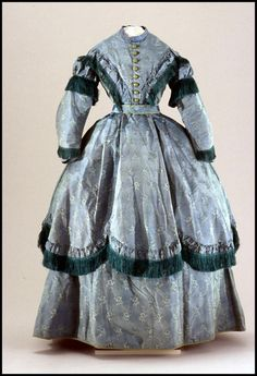 Day dress, changeable blue-green ribbed silk, Europe or America, ca. 1867. Woven with floral sprigs, trimmed with green silk fringe & puffed bands of self-fabric. High round neckline & center front button closure. Upper sleeves trimmed with puffed & fringed self-fabric with extra fringe at wrist. Flounced overskirt trimmed with fringe. Boned bodice, attached belt. Lined with glazed cotton.