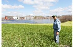 Leonard Dinter stands in front of his home near Aberdeen which is completely flooded, July 10, 2014. lived here since 1903