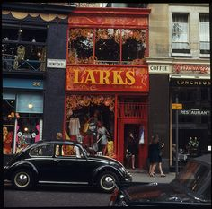 This 1960s photo showing the exterior of Larks & Sparks in Brompton Road, Knightsbridge captures the vibrant street life of Carnaby & Brompton at a time when Carnaby was becoming a mecca for the young & mod. The cars, fashion, laneways, shops window displays, (note the dress printed with a photograph of Bob Dylan positioned in the window) painted murals and typography captured in David Mist's photos reflect the gay, carnival, counter-culture atmosphere of inner city London during this…