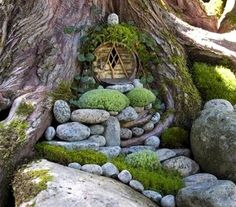 Fairy garden at the base of a tree. Love the use of river rocks and moss. We have plenty of those!