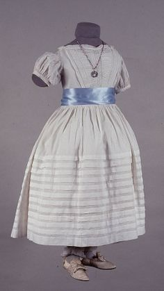 1815 Children's Dress - white cotton dress with very low neck and short puff sleeves.  The bodice is decorated with Ayrshire embroidery.