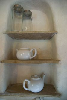 Built in stone shelves in a cob house - thick walls mean lots of extra storage solutions