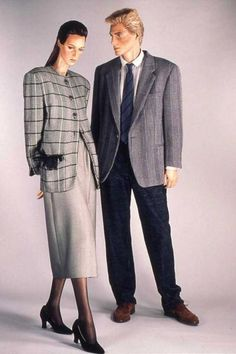 1986 : Man's jacket, trousers, shirt and brogues, by Giorgio Armani. Woman's checked wool jacket, grey skirt & black suede shoes, by Giorgio Armani